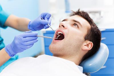 man at emergency dental appointment | Clinton township